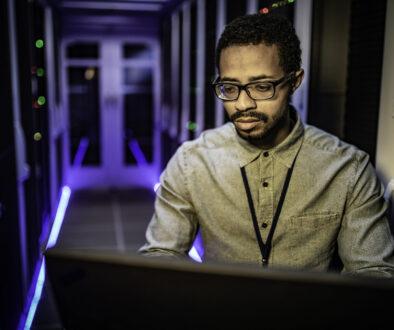 IT technician doing regular server maintenance on his laptop